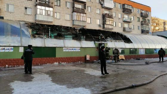 Сотрудники экстренных служб стоят возле горевшего здания магазина