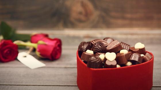 Красная коробка с маленькими шоколадными сердцами стоит на столе, рядом лежат три красные розы