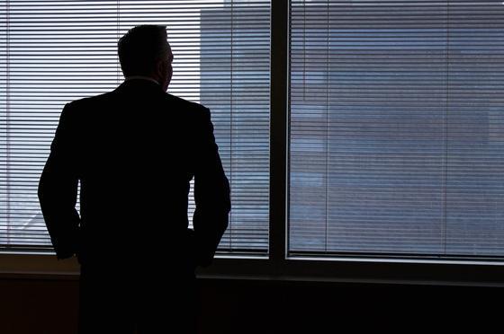 Мужчина смотрит в окно офиса
