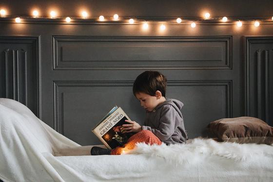 Мальчик сидит на кровати с книгой в руках