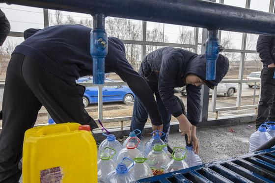 Мужчины набирают воду на колонке