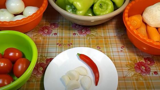 В мисках лежат помидоры, лук, перец, морковь, сельдерей, дольки чеснок и острый перец