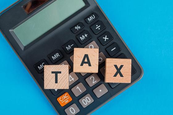 Кубики с надписью Tax лежат на калькуляторе
