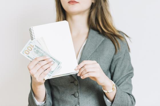Женщина держит блокнот и деньги