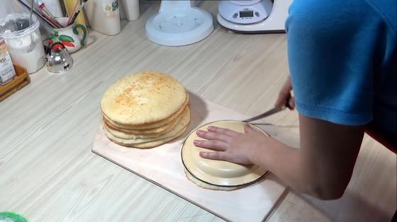 Человек делает одинаковыми коржи для торта