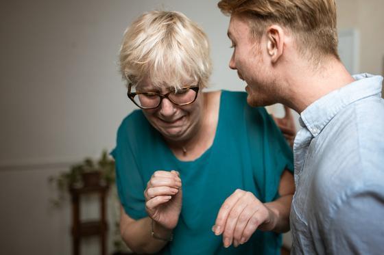 Молодой человек кричит на престарелую мать