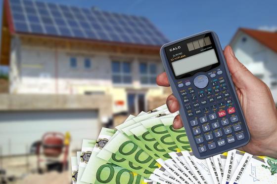 Мужчина держит в руке калькулятор на фоне дома и денежных купюр