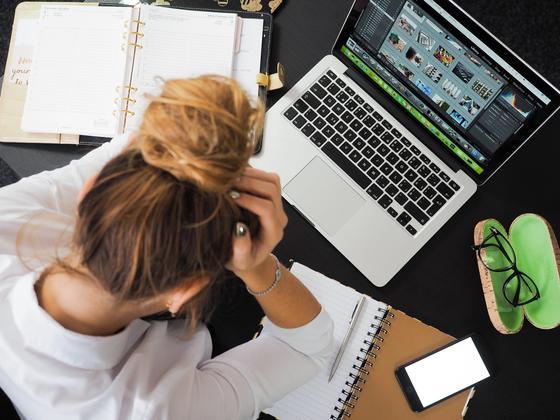 Девушка держится за голову, сидя за компьютером