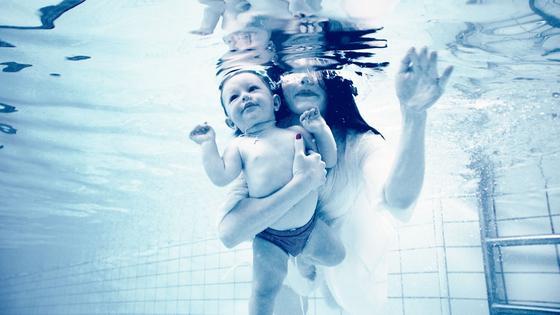 Мама с малышом купаются в бассейне