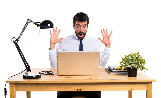 Мужчина за рабочим столом в ужасе