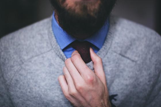 Мужчина в свитере поправляет галстук
