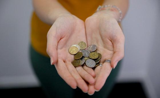 Девушка держит в руках монеты казахстанской валюты