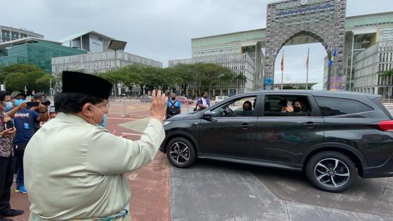 Отец жениха приветствует гостей на машинах