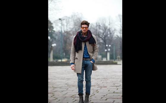 Мужчина в пальто стоит на площади