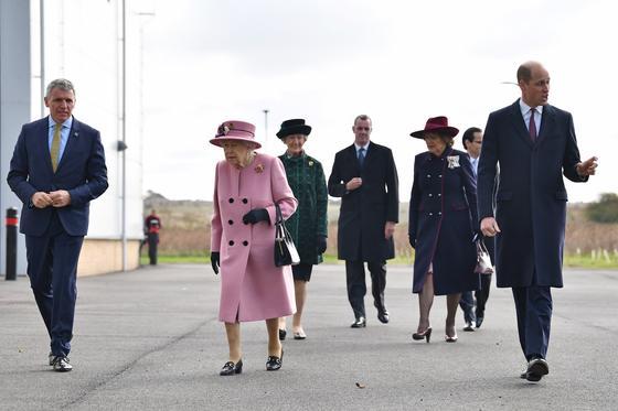 Королева идет в сопровождении сотрудников центра