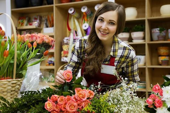 Девушка продает цветы в магазине