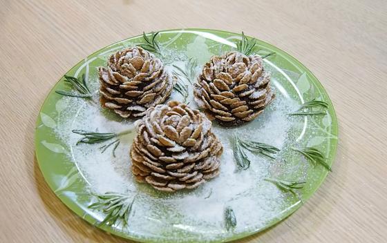 Печенье шишки с сахарной пудрой на зеленой тарелке