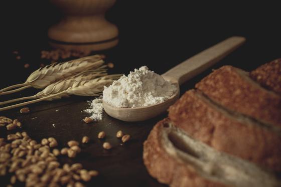 Пшеница, мука, хлеб лежат на столе