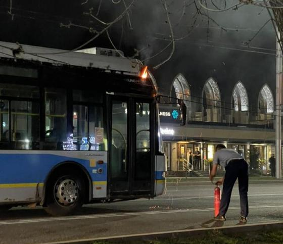 Водитель троллейбуса держит в руках огнетушитель