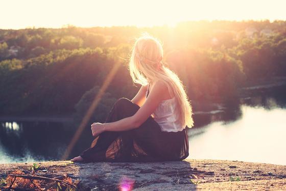 Девушка сидит на берегу озера