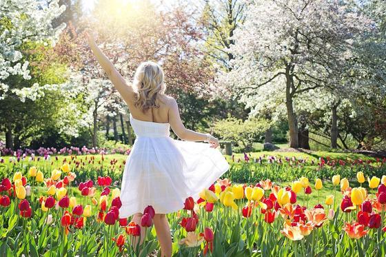 Девушка идет по полю с тюльпанами