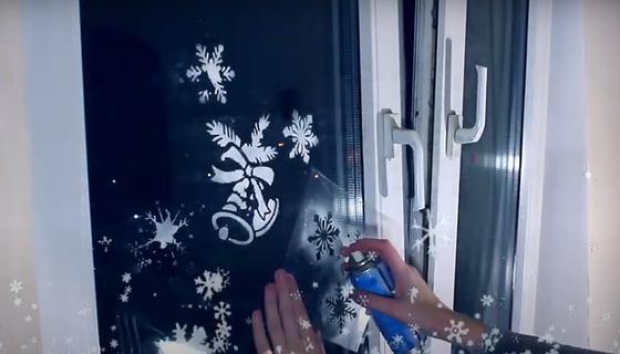 Девушка рисует снежинки с помощью трафарета