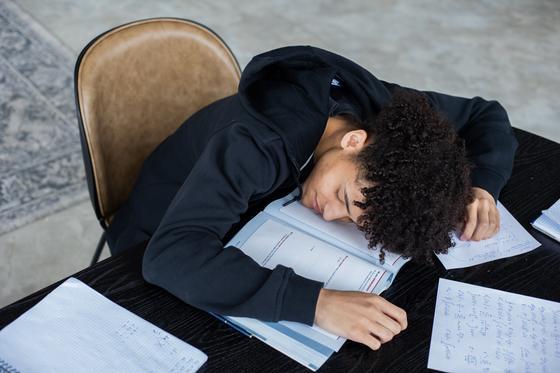 Парень спит на открытых книгах и тетрадях, сидя за столом