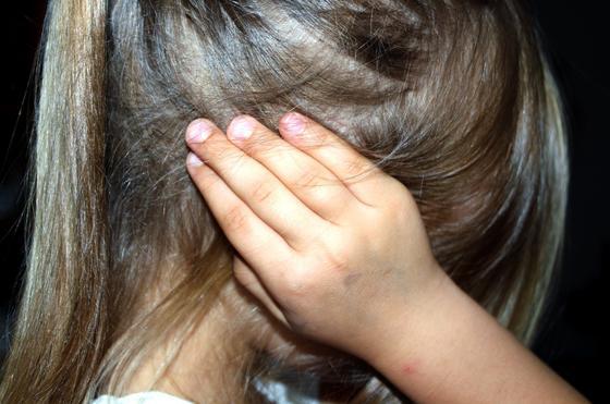 Девочка закрывает ухо рукой