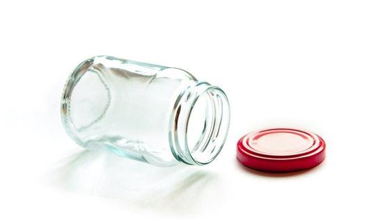 На столе лежит чистая банка с красной винтовой крышкой