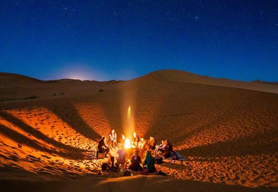Люди сидят у костра в пустыне