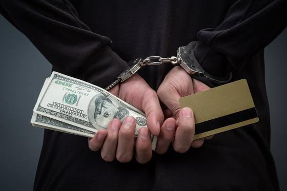 Человек в наручниках с деньгами и картой