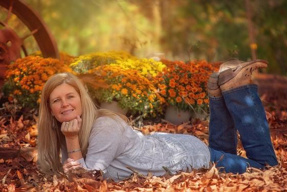 Девушка лежит на сухих листьях на фоне горшков с цветами