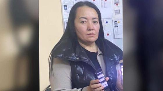 Женщина, подозреваемая в мошенничестве, держит в руках телефон