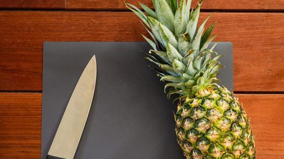 Нож и спелый ананас на дощечке