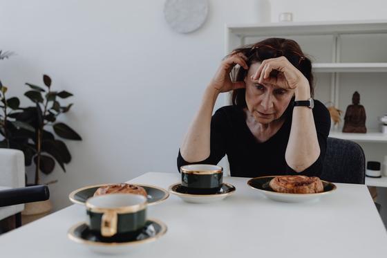 Женщина сидит за обеденным столом, подперев рукаи голову