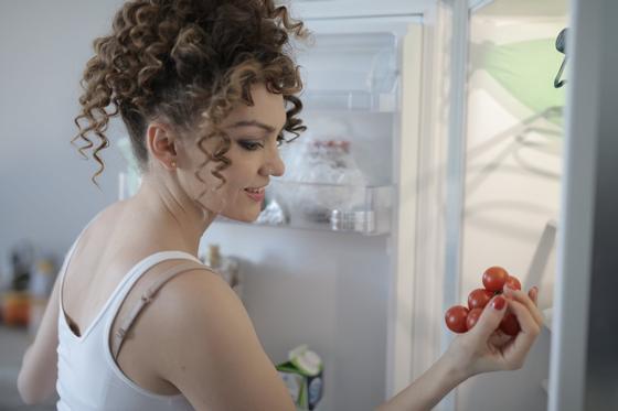 Девушка стоит возле холодильника и держит в руках помидоры