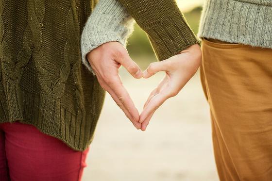Девушка и парень соединили руки в виде сердца
