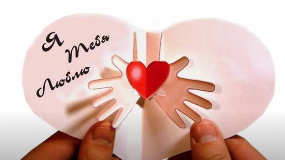 В руках держат бумажную открытку в форме сердца с красным сердечком и ладонями по центру и надписью