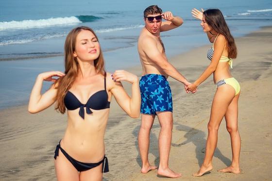 Парень идет с девушкой по пляжу и смотрит на другую
