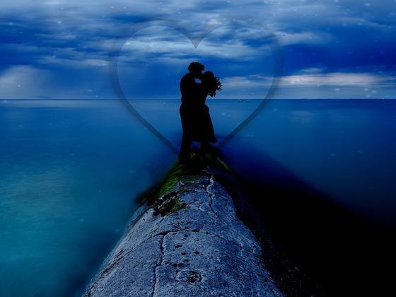 Пара целуется на фоне неба и океана