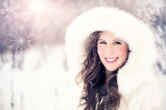 Девушка улыбается на фоне снежинок