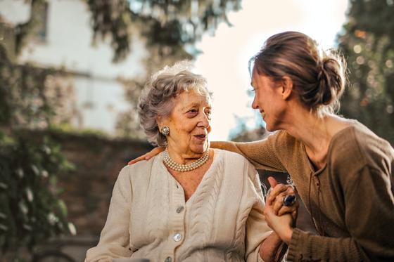 Молодая женщина разговаривает со старушкой в саду