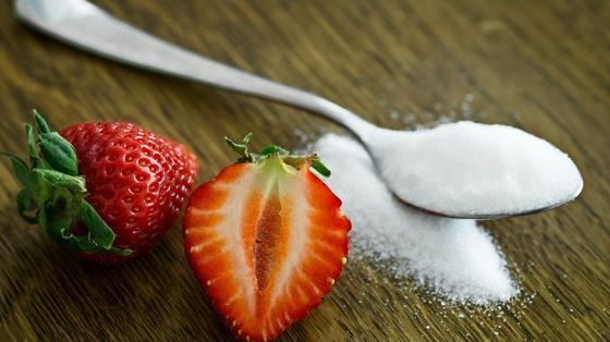 На столе ложка с сахаром и разрезанные ягоды клубники
