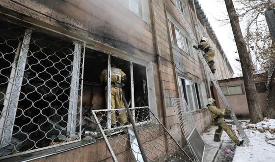 Пожарный стоит в окне здания