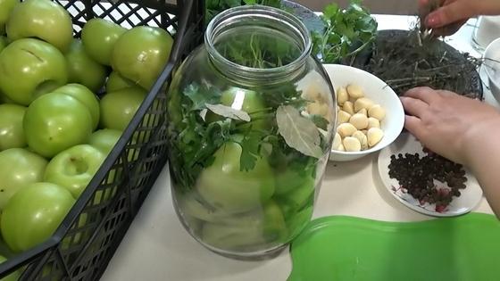 Зеленые помидоры в ящике и в банке с зеленью и специями