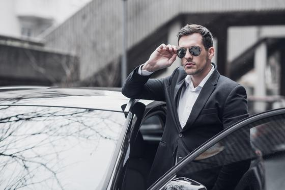 Мужчина в деловом костюме садится в автомобиль