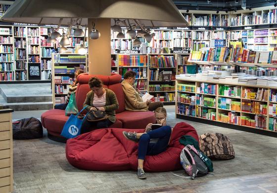Люди в мягких креслах и читают в книжном магазине