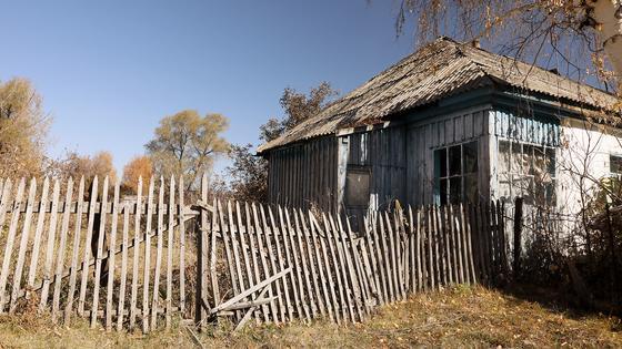 полуразрушенный дом со старым забором стоит у дороги
