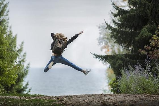Девушка с рюкзаком в прыжке в воздухе