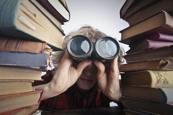 Парень в клетчатой рубашке с биноклем между двумя стопками книг